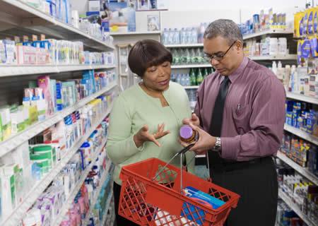 homme et femme regardant une bouteille de suppléments et son étiquette