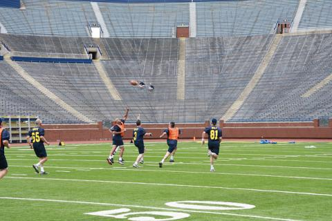 Several men run on the Michigan Stadium field to catch a pass